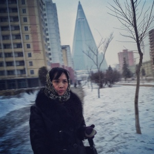 In this January 15, 2013 photo taken with an iPod Touch and originally posted to Instagram from Pyongyang, a woman walks on a Pyongyang street in front of the pyramid-shaped 105-story Ryugyong Hotel, which North Korea began building in 1987 and it is yet to be complete. (AP Photo/David Guttenfelder)