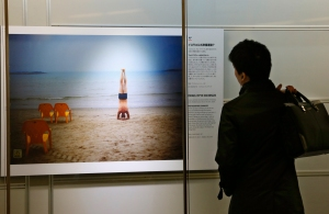 A man looks at a photograph at the AP Photo exhibition at Tokyo Station gallery in Tokyo, Thursday, Jan. 9, 2014. (AP Photo/Shizuo Kambayashi)