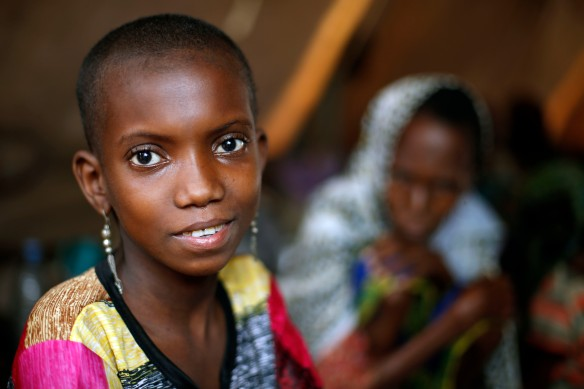 In this April 16, 2014 photo, 10-year-old Hamamatou Harouna smiles as she sits in a tent with other Muslim refugees on the grounds of the Catholic Church in Carnot, Central African Republic. (AP Photo/Jerome Delay)