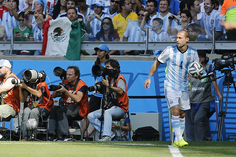 Frankfurt-based AP photographer Martin Meissner, third from left, covers the group F World Cup soccer match between Argentina and Iran as Argentina's Pablo Zabaleta, right, stands with the ball on the sideline at the Mineirao Stadium in Belo Horizonte, Brazil, Saturday, June 21, 2014. (AP Photo/Victor R. Caivano)