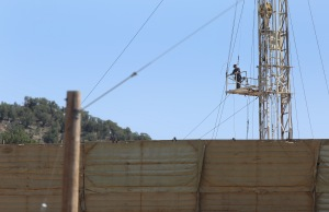 In this June 9, 2014 photo, a petroleum industry worker stands on an oil and gas rig on a well pad, in New Castle, a small farming and ranching settlement on the Western Slope of the Rockies, in Colo. (AP Photo/Brennan Linsley)
