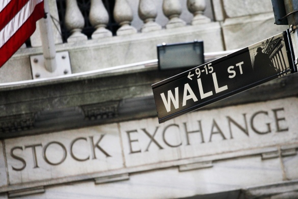 This July 16, 2013 file photo shows a street sign for Wall Street outside the New York Stock Exchange in New York. U.S. stock futures are steady Wednesday, May 28, 2014, with the market market hovering at record levels. (AP Photo/Mark Lennihan, File)