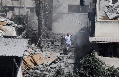 A Palestinian man stands in the rubble of a house after it was hit by an Israeli missile strike in Gaza City, Friday, July 18, 2014. Israel intensified its 11-day campaign against Hamas by sending in tanks and troops late Thursday after becoming increasingly exasperated with unrelenting rocket fire from Gaza on its cities, especially following Hamas' rejection of an Egyptian cease-fire plan earlier in the week. (AP Photo/Hatem Moussa)