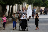 A Palestinian wheels an elderly woman as they flee their homes in the Gaza's Shijaiyah neighborhood, northern Gaza Strip, Sunday, July 20, 2014. A Gaza City neighborhood came under heavy tank fire Sunday as Israel widened its ground offensive against Hamas, causing hundreds of panicked residents to flee, including a woman in a wheelchair waving a white flag. (AP Photo/Hatem Moussa)
