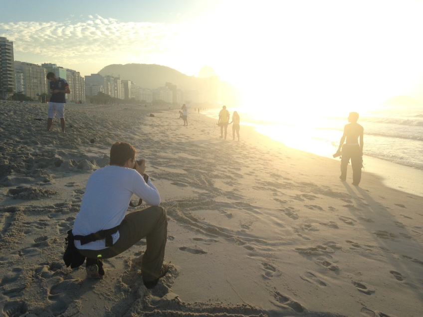London-based photographer Matt Dunham shoots pictures on the Copacabana beach at sunrise. (Photo by Rob Harris)