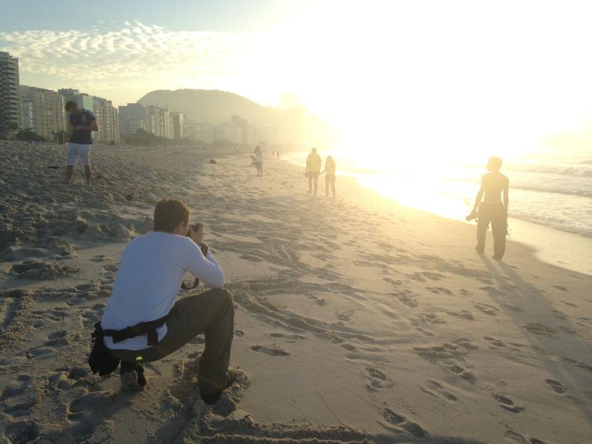 London-based photographer Matt Dunham shoots pictures on the Copacabana beach at sunrise. (Photo by Rob Harris)