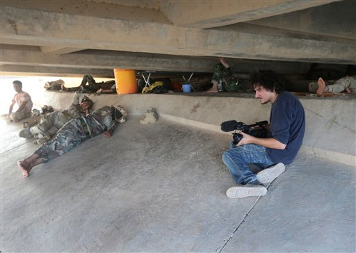 This July 1, 2014 photo shows Associated Press video journalist Simone Camilli at work filming Kurdish Peshmerga fighters under a bridge near the front line with militants from the Islamic state group, in Mariam Bek village, between the northern cities of Tikrit and Kirkuk, Iraq. Camilli, 35, was killed in an ordnance explosion in the Gaza Strip, on Wednesday, Aug. 13, 2014 together with Palestinian translator Ali Shehda Abu Afash and three members of the Gaza police. Police said four other people were seriously injured, including AP photographer Hatem Moussa.(AP Photo/Hussein Malla)