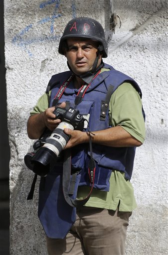 In this Saturday, Aug. 2, 2014 photo, Associated Press photographer Hatem Moussa works, in Gaza City, Gaza Strip. Moussa was seriously injured Wednesday when Gaza police engineers were neutralizing unexploded ordnance in the Gaza town of Beit Lahiya left over from fighting between Israel and Islamic militants. (AP Photo)