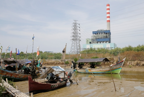 In this Oct. 18 , 2014 photo, fishing boat passes near a fired coal power plant on the river in Cirebon. The coal-fired power plant in Cirebon came online two years ago despite years of protests from environmentalists and villagers who say the plant is polluting coastal waters, killing off fish and crabs.  (AP Photo/Achmad Ibrahim)