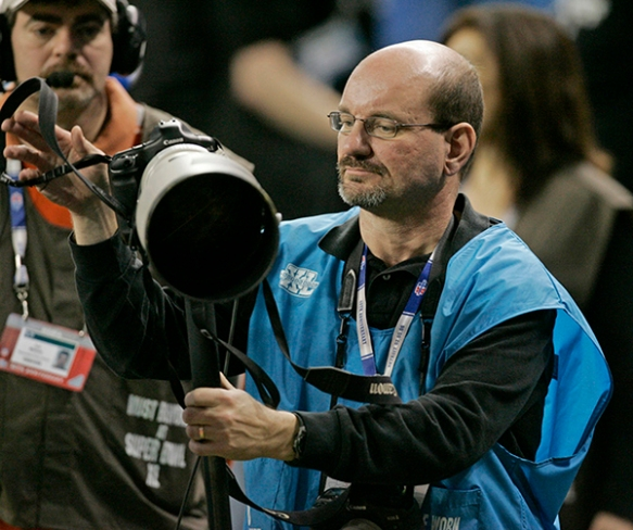 Indianapolis-based photographer Mike Conroy on the field at the start of the NFL Super Bowl XL Feb. 5, 2006 in Detroit, Michigan. (AP Photo/Amy Sancetta)