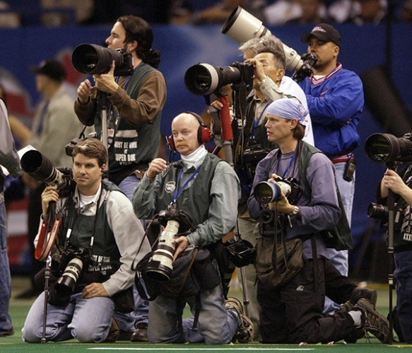 Photographer Doug Mills, center, at the NFL Super Bowl XXXVI in New Orleans, Feb. 3, 2002. (AP Photo/Mark Duncan)