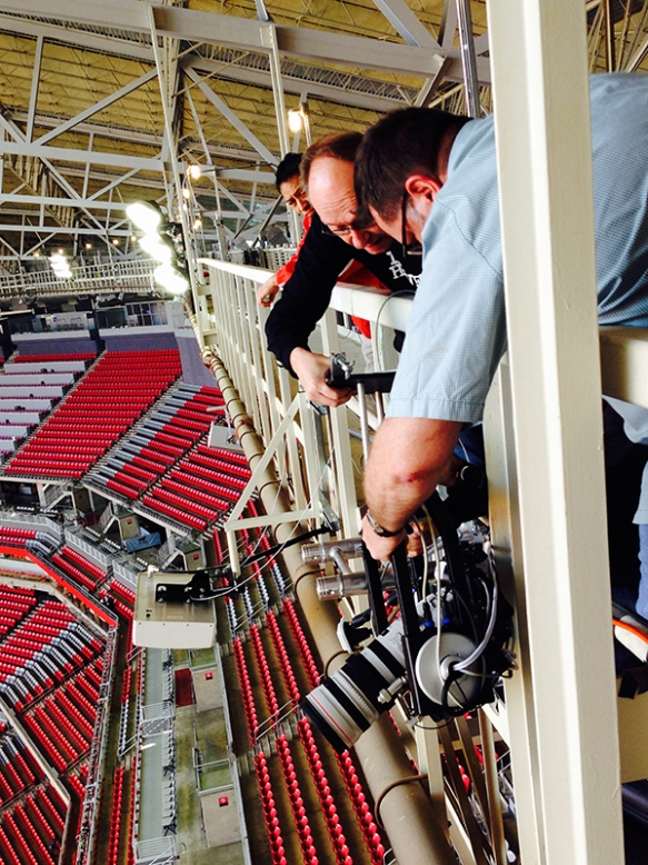 Technology specialist Jorge Nunez, far left, watches as Global Photo Operations Manager Tim Donnelly and Houston-based photographer David Phillip, right, install a robotic camera on the catwalk in preparation for Super Bowl XLIX, Saturday, Jan. 24, 2015. (Photo by Denis Paquin)