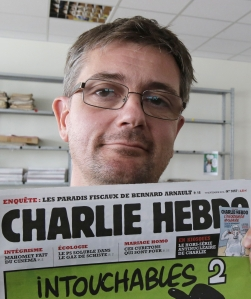 In this Sept.19, 2012 file photo,  Stephane Charbonnier also known as Charb ,  the editor of the satirical weekly Charlie Hebdo, displays the front page of the newspaper as he poses for photographers in Paris. AP moved this image on the wire this week. (AP Photo/Michel Euler, File)