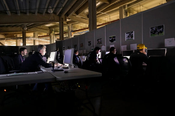 Deputy Director of Photography Denis Paquin, front left, and colleagues edit during the Super Bowl blackout, Sunday, Feb. 3, 2013, at the Superdome in New Orleans. (AP Photo/ Julie Jacobson)