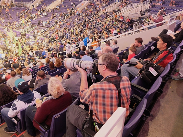 Photographer Charlie Riedel takes photos from the stands during the NFL Super Bowl XLIX Media Day at the U.S Airways Arena in Phoenix, Ariz., Tuesday, Jan. 27, 2015. (AP Photo/Carolyn Kazdan)