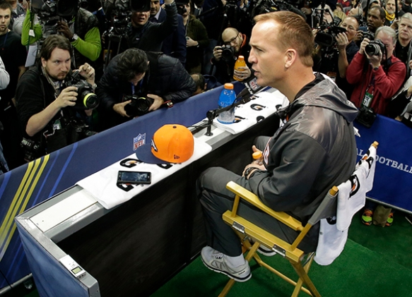 Photographers Matt Slocum, left, and Mark Humphrey, right, in red, covering Denver Broncos Peyton Manning during media day for the NFL Super Bowl XLVIII football game Tuesday, Jan. 28, 2014, in Newark, N.J. (AP Photo/Charlie Riedel)
