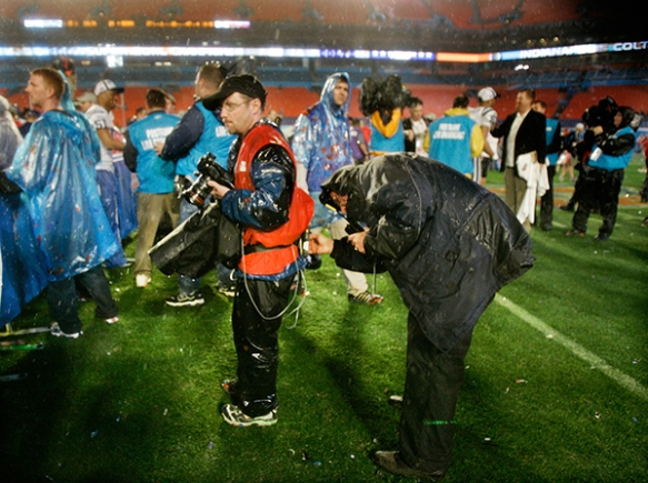 Global Photo Operations Manager Tim Donnelly, right, checks St. Louis-based photographer Jeff Roberson's transmitting device on the field following the NFL Super Bowl XLI Feb. 4, 2007 in Miami, Florida. (AP Photo/Amy Sancetta)