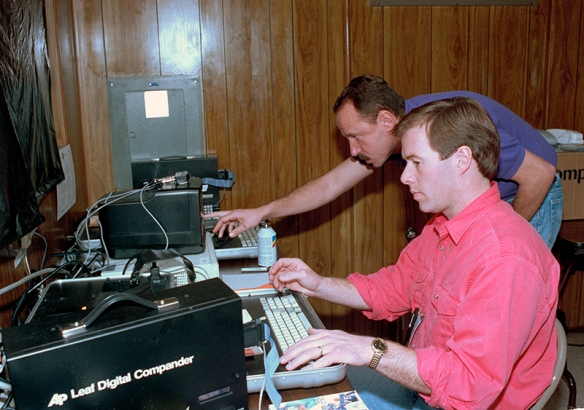 Photographers Mark Humphrey, foreground, of Nashville and Cliff Schiappa of Kansas City work at Leafax negative transmitters, sending photos from a trailer for the NFL Super Bowl XXV football game in Tampa, January 1991. (AP Corporate Archives photo)