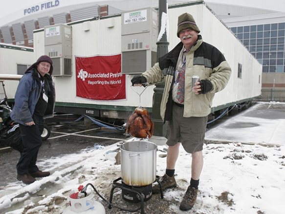 Photographer and South Regional Editor Dave Martin, center, deep fries a turkey outside the AP photo trailer at the Super Bowl in Detroit, Sunday, Feb. 5, 2006. Standing to the left of Martin is Global Photo Operations Manager Tim Donnelly. It had become a tradition for Martin to deep fry turkeys at major events for the enjoyment of AP staff and other journalists. Martin died after collapsing on the Georgia Dome field while covering the Chick-fil-A Bowl in Atlanta, Jan. 1, 2014. (AP Photo/Cliff Schiappa)