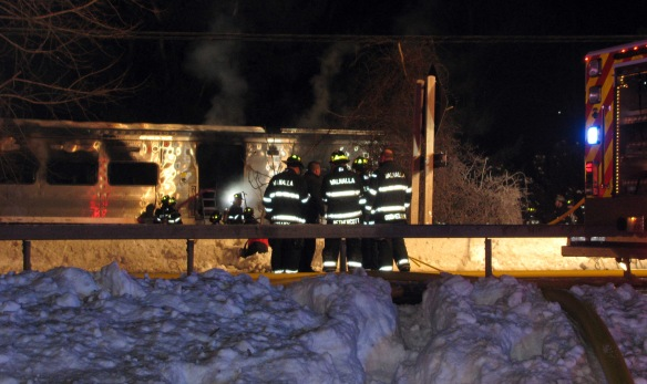 Firefighters work at the scene of an accident in Valhalla, N.Y., Tuesday, Feb. 3, 2015. A packed commuter train slammed into a sport utility vehicle on the tracks and the front of the train and the vehicle burst into flames, authorities said. (AP Photo/Kiley Armstrong)