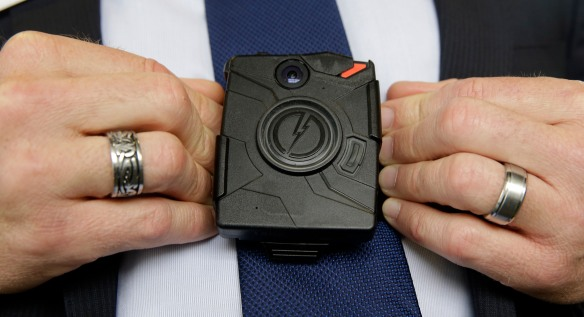 In this Feb. 19, 2015 file photo, Steve Tuttle, vice president of communications for Taser International, demonstrates one of the company's body cameras for The Associated Press during a company-sponsored conference hosted by Taser at the California Highway Patrol Headquarters in Sacramento, Calif. Officials in Salt Lake City and Fort Worth, Texas, said they are reviewing their ethics policies after The Associated Press reported on how their police chiefs were closely linked to the company that won contracts to supply officers with body cameras. (AP Photo/Rich Pedroncelli)