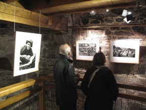 """In this Saturday, April 11, 2015 photo, a couple looks at photos at the exhibit """"Henri Huet: Vietnam"""" at the the Tour Bidouane in St Malo, western France. The exhibition commemorates the work of AP Photographer Henri Huet during the Vietnam war before he perished when his helicopter was shot down over Laos 44 years ago. The Exhibition ends on May 8, 2015. (AP Photo/Laurent Rebours)"""