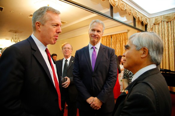 "Seen from left to right, U.S. Ambassador to Vietnam Ted Osius, Canadian Ambassador David Devine, AP President and CEO Gary Pruitt and AP photographer Nick Ut chat June 11 at the opening reception in Hanoi, Vietnam, for AP's photo exhibit. Ut's iconic ""Napalm Girl"" image is among those on display. (AP Photo/Wong Maye-E)"