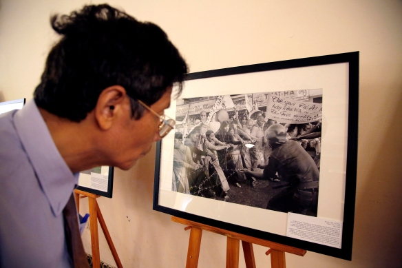 "A guest looks at photographs taken by Horst Faas during the opening reception of The Associated Press photo exhibit, Thursday, June 11, 2015, in Hanoi, Vietnam.  The exhibit ""Vietnam: The Real War,"" a collection of 58 photographs taken by AP photographers during the Vietnam War that ended 40-years ago, opens to the public Friday, June 12, 2015, in Hanoi. (AP Photo/Wong Maye-E)"