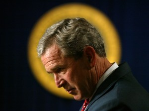 Concerns have been raised about a glow or halo around the president since George W. Bush held office, as seen in this frame with the presidential seal behind him. The out-of-focus seal is simply a tool to separate the subject from the background so he is not seen speaking in a sea of black. (AP Photo/Charles Dharapak)