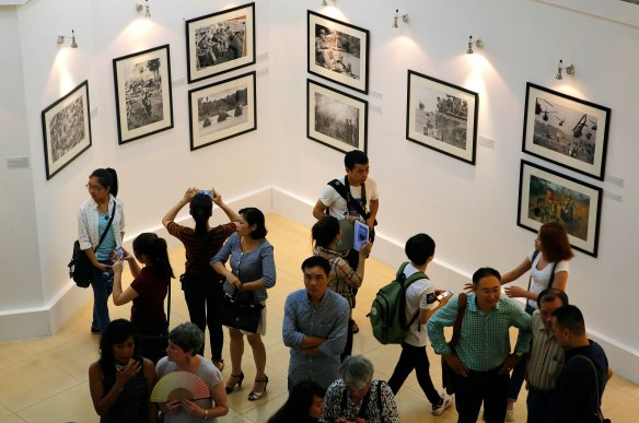 "Guests and members of the public view photos from the Vietnam War on display at an exhibit Friday, June 12, 2015, in Hanoi, Vietnam. ""Vietnam: The Real War,"" a collection of 58 photographs taken by the Associated Press, opens to the public Friday, marking a homecoming that officials say is historic and an emblem of changing times. (AP Photo/Wong Maye-E)"