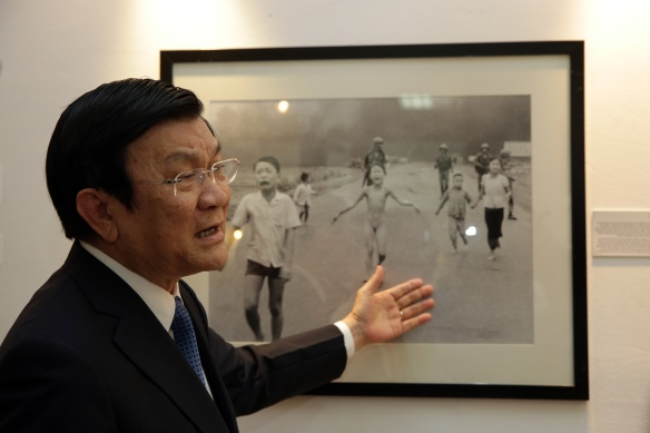 "Vietnam President Truong Tan Sang talks to the media in front of ""Napalm Girl,"" the Pulitzer Prize-winning photo taken by Nick Ut, during his visit on Monday, June 15, to an exhibit of AP's Vietnam War photos in Hanoi. (AP Photo/Na Son Nguyen)"