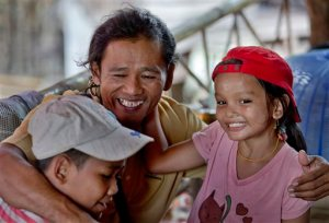 In this May 16, 2015 photo, former slave fisherman Myint Naing, center, hugs his niece Kyi Wai Hnin, right, and nephew Kyaw Min Tun following his return to his village in Mon State, Myanmar. Myint, 40, is among hundreds of former slave fishermen who returned to Myanmar following an Associated Press investigation into the use of forced labor in Southeast Asia's seafood industry. (AP Photo/Gemunu Amarasinghe)
